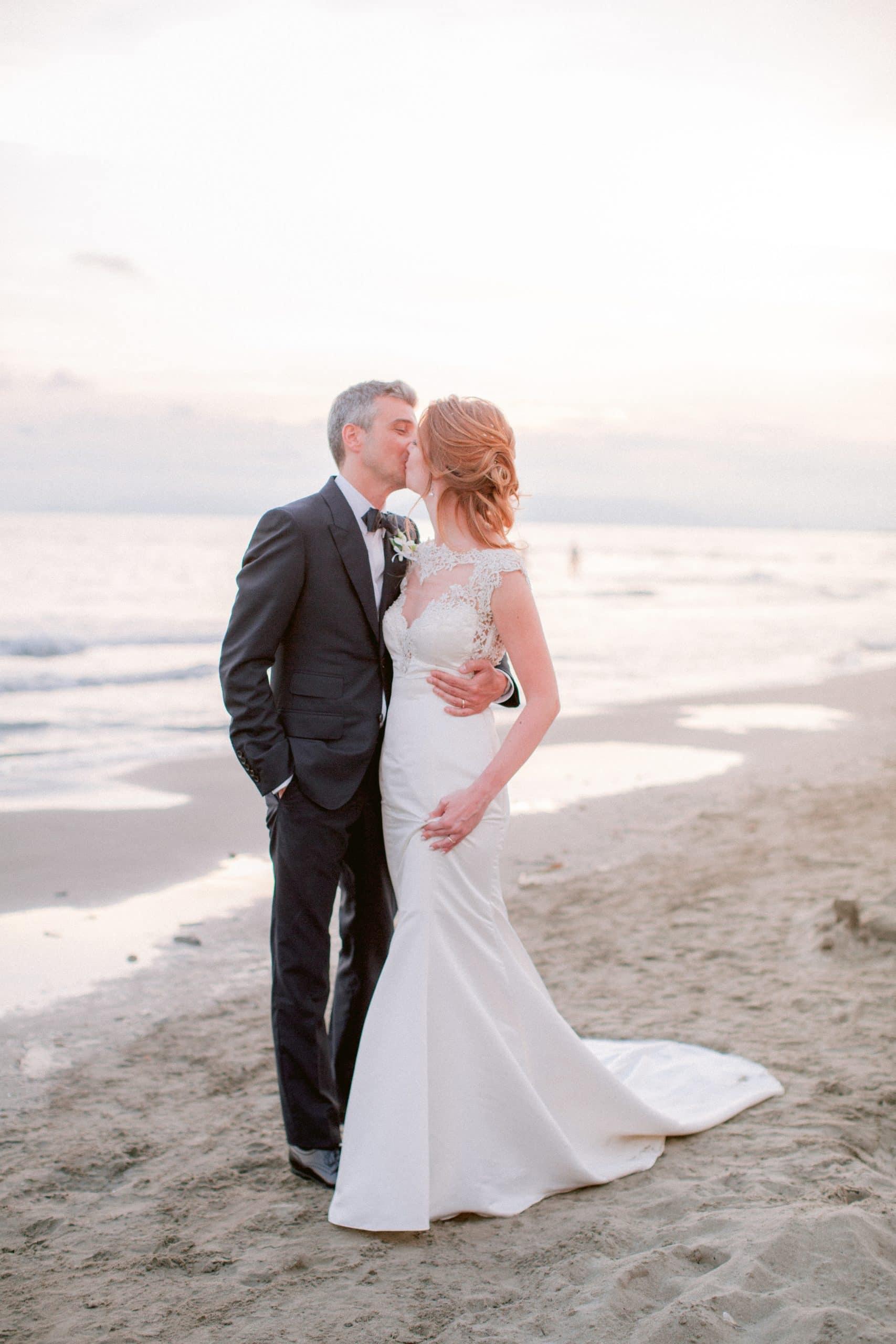 una passeggiata sulla spiaggia al tramonto da parte di due sposi novelli